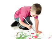 Little kid pressing foam on canvass — Stock Photo