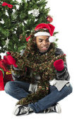 Man wrapped in christmas decorations — Stock Photo