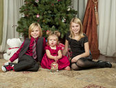 Portrait of brother and sisters sitting on floor with christmas — Foto Stock