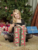 Portrait view of a girl opening a gift box — Stock Photo