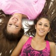 Portrait of smiling teenage girls lying on back — Stock Photo