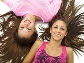 Portrait of smiling teenage girls lying on back — Stock Photo