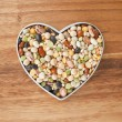 Assorted beans on a heart shape container — Stock Photo