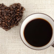 Black coffee with heart shape beans — Stock Photo