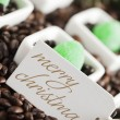 Close up of merry christmas tag with coffee beans and candies — Stock Photo