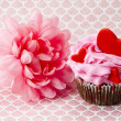 Close up shot of a strawberry cupcake and a flower — Stock Photo