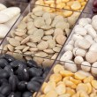Cropped image of variety of food grains in glass partition — Stock Photo