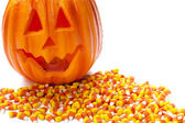 Carved pumpkin on pile of candy corn — Stock Photo