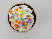 Chocolate cupcake with white icing and colorful sprinkles — Stock Photo