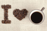 Coffee beans and coffee cup forming i love you — Stock Photo