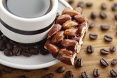 Cropped image of coffee cup with confection and coffee beans — Stock Photo