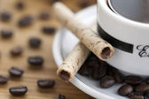 Cup and saucer coffee beans with cookie sticks — Stock Photo