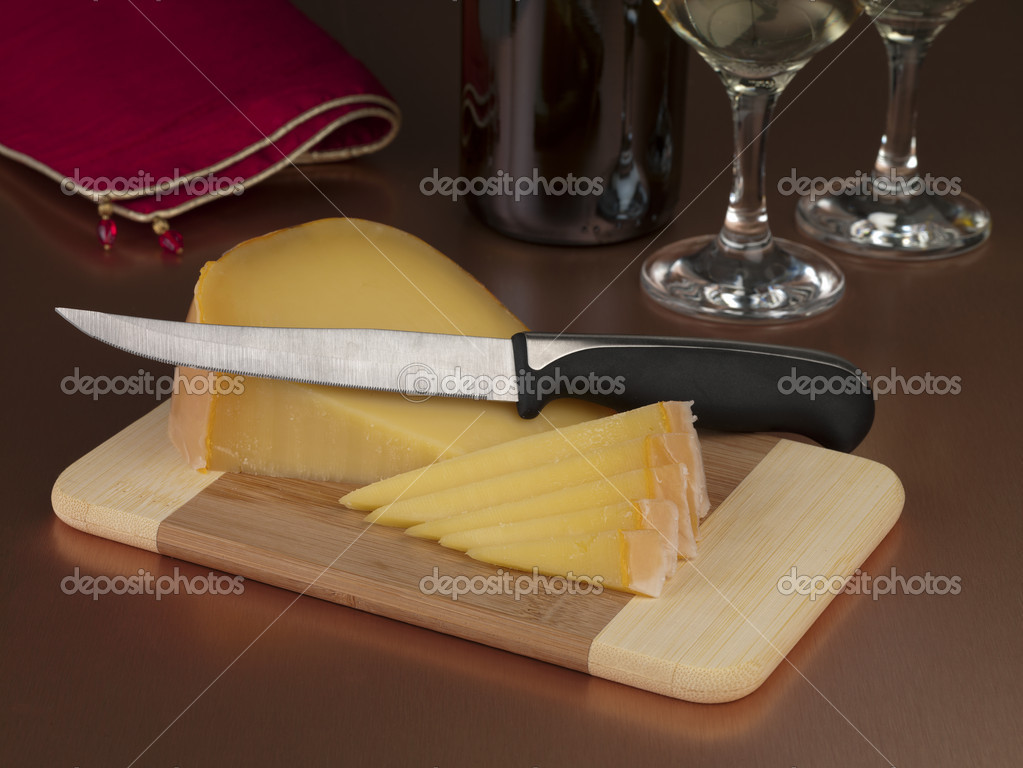 Italian cheese on top of a wooden chopping board and knife — Stock Photo #18399277