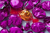 Shiny golden candy arranged in between of purple hard candies — Stock Photo