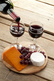 View of a board with cheese and grapes while someone pouting win — Stock Photo