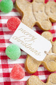 View of a merry christmas tag with gingerbread candies — Stock Photo