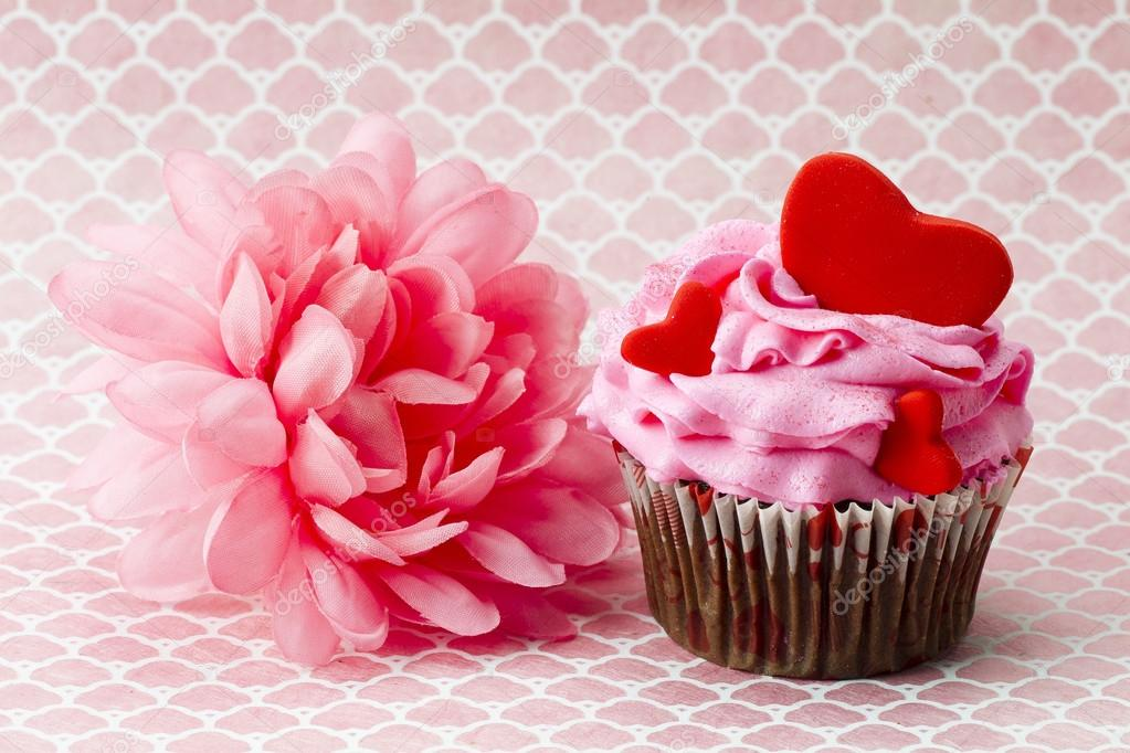 Close-up shot of strawberry cupcake with heart shape and pink flower.  Foto de Stock   #18401353