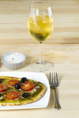 Baked pizza with wineglass on table — Stock Photo