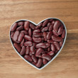 Red haricot on a heart shape container — Stock Photo