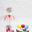 Cupcake with white icing and balloon and birthday sign — Stock Photo #18739057