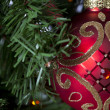 Cropped view of shiny red christmas bulb hanging on christmas tr - Lizenzfreies Foto