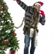 Happy young man gesturing while decorating christmas tree - Lizenzfreies Foto