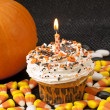 Halloween cupcake with lighted candle - Stock Photo