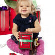 Portrait of a cheerful baby girl sitting with christmas gift box — Stock Photo