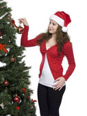 Beautiful young woman decorating christmas tree — Stock Photo