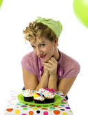 Beautiful young woman with a plate of cupcakes — Stock Photo