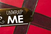 An unwrap me tag on a christmas present — Stock Photo