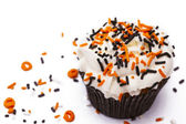 Cupcake with white icing decorated with sprinkles — Stock Photo