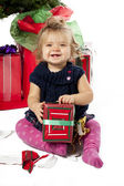 Portrait of a cheerful baby girl sitting with christmas gift box — Foto Stock