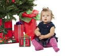 Retrato de uma doce menina sentada pela árvore de natal e natal — Foto Stock