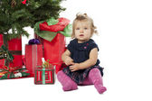Portrait of a sweet girl sitting by christmas tree and christmas — Fotografia Stock