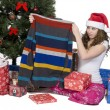 Pretty young woman looking at her christmas present — Stock Photo #18740131