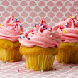 Three strawberry cupcakes with sugar icing and sprinkles - Lizenzfreies Foto