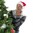 Surprised africamericmlooking at christmas tree — Stock Photo #18740669