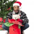 Surprised african american man with his christmas present - Lizenzfreies Foto