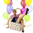 Stock Photo: Young womsitting in box with balloons on side
