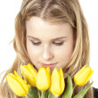 Close up of a young woman with yellow tulips - Stock fotografie