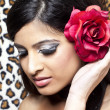 Beautiful young female with red flower in hair — Stok fotoğraf