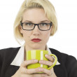 Serious look of female office staff holding a mug - Stock Photo