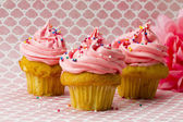 Three strawberry cupcakes with sugar icing and sprinkles — Stock Photo