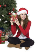 Woman wearing a santa costume holding a gift — Stock Photo
