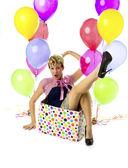 Jovem mulher sentada em uma caixa com balões do lado — Foto Stock