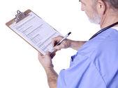 Un médico con una escritura médica portapapeles — Foto de Stock
