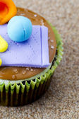 Close cropped image of a cupcake with miniature looking items on — Stock Photo