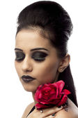 Beautiful young woman holding rose with eyes closed — Stock Photo