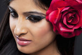 Close up shot of a woman with a rose in her hair — Stock Photo